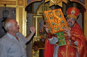 Archimandrite Oleg accepts the gift of the altar Gospel at Church of All Saints