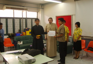 Chairman of Orthodox Church in Thailand Foundation deacon Daniel Wanna presents the paychecks to those students who proved worthy the educational grants of the Foundation.