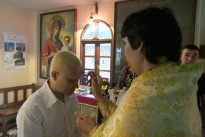 Priest Roman Bychkov anoints the newly baptized Mr. Vitaly with Holy Myrrh